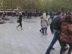 Passanten eilen über den Breitscheidplatz. Im Hintergrund hat ein Schausteller gerade seine Vorstellung beendet.