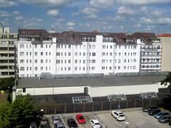 Rückseite des Gebäudes; die Kellergarage mit ihren vier Oberlichtern erstreckt sich bis zum Zaun im Vordergrund
