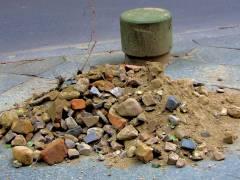 Ein Steinhaufen und ein Poller am Straßenrand